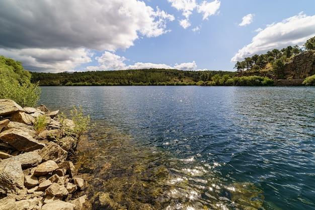 Lago com nuvens, céu azul e reflexos na água. reservatório atazar madrid, espanha,