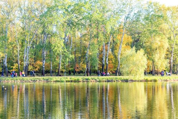 Lago com pássaros no parque da cidade de outono e pessoas caminhando