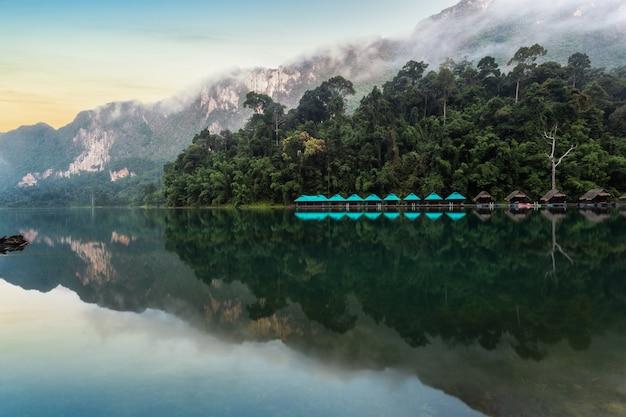 Lago com reflexo da paisagem de floresta e montanhas