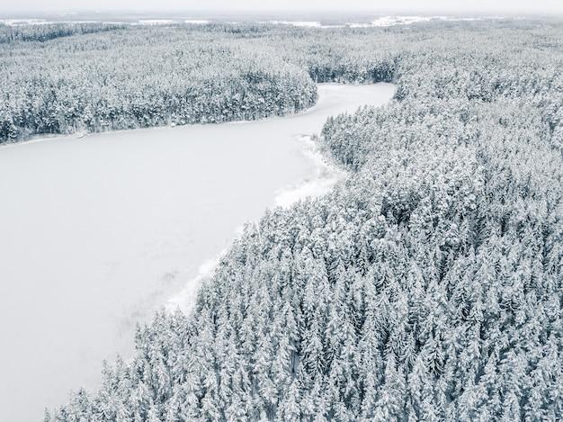 Lago congelado com parque nacional coberto de neve no fundo - foto do drone