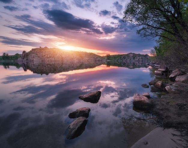 Lago contra o céu colorido com nuvens ao pôr do sol
