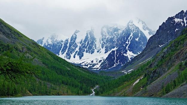 Lago de bela montanha com águas cristalinas turquesa no altai. montanhas altas com neve e árvores