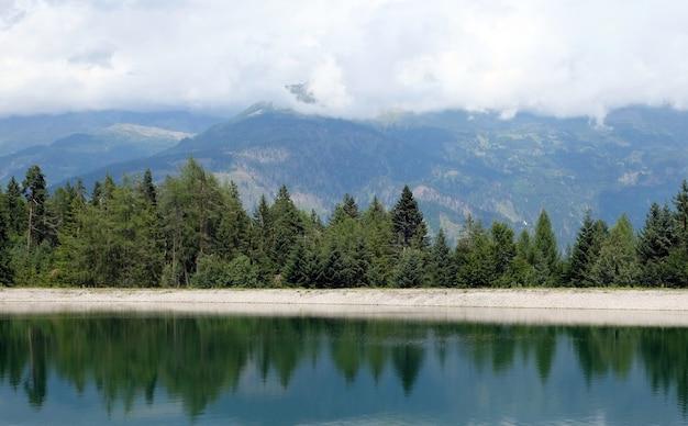 Lago de montanha azul com grama e nuvens de árvores, céu azul
