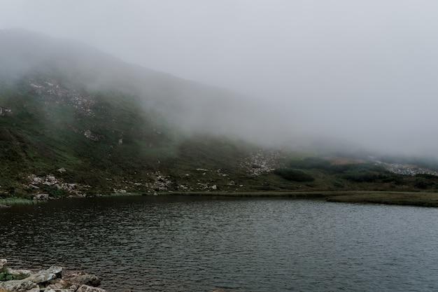 Lago de montanha cheio de nevoeiro em dia chuvoso