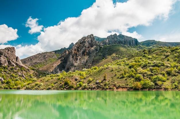 Lago de montanha com água verde brilhante, grande pedra em primeiro plano na costa