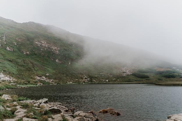 Lago de montanha e em dia de nevoeiro