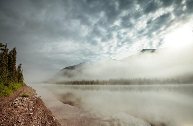 Lago de montanha enevoada no início da manhã serena nas montanhas.