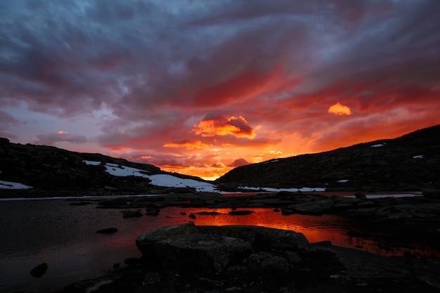 Lago de montanha, paisagem norueguesa ao pôr do sol