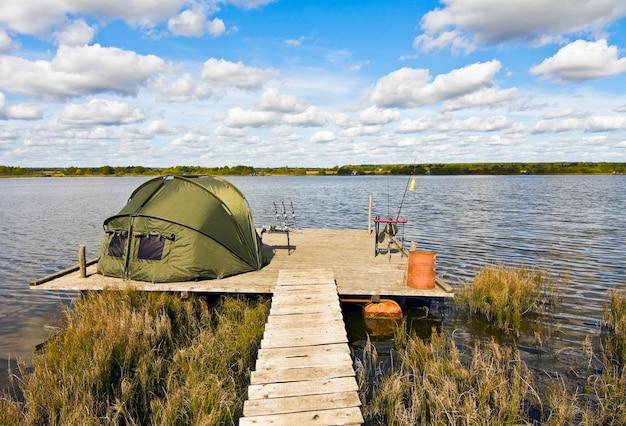 Lago de pesca com uma barraca de acampamento