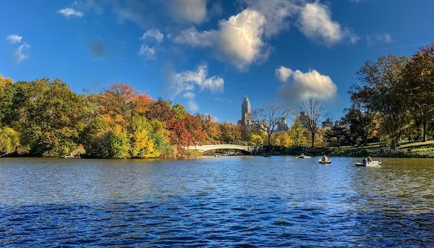 Lago de um parque urbano com pessoas remando em barcos no outono em nova york