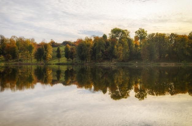 Lago e bela paisagem de outono com reflexo