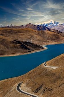 Lago e estrada yamdrok yumtso no tibete com nuvens brancas finas no céu