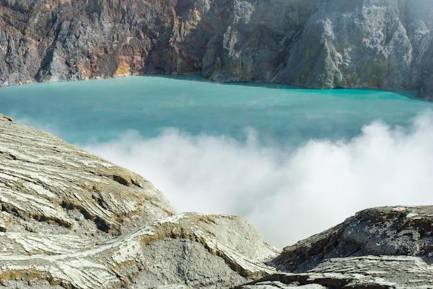 Lago expulsando a fumaça cercada por rochas
