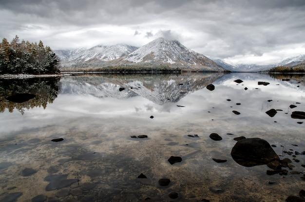 Lago froliha da montanha, pinheiro e pedras através da água transparente com neve no lago do espelho