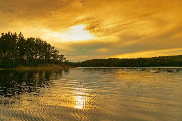 Lago ladoga ao pôr do sol. nuvens vermelhas e amarelas brilhantes da cor do céu.