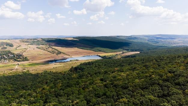 Lago localizado na planície, floresta em primeiro plano e colinas