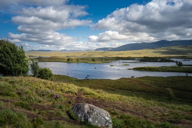 Lago loch tulla cercado por montanhas e prados no reino unido