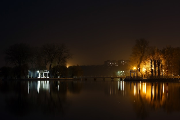 Lago na noite com uma casa e luzes