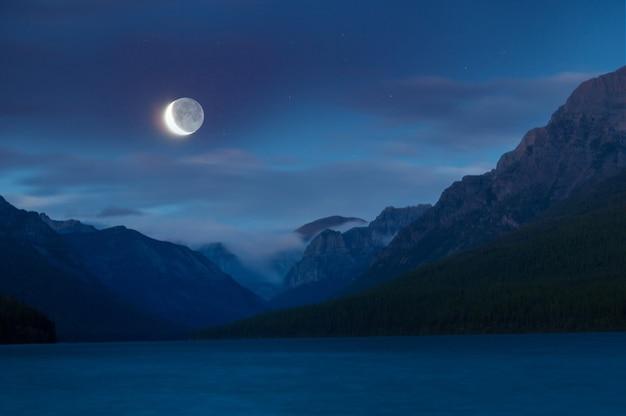 Lago nas montanhas à noite sob a luz da lua