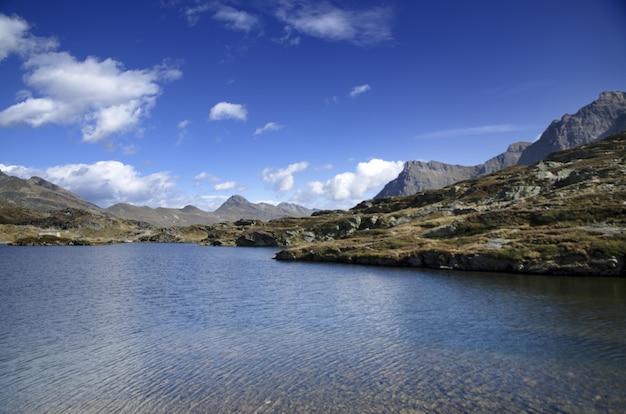 Lago panorâmico cercado por montanhas em um dia ensolarado