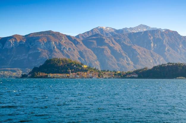 Lago panorâmico com uma vila costeira no horizonte e montanhas contra o céu azul