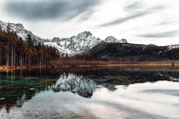 Lago perto de montanha coberta de neve sob céu nublado durante o dia
