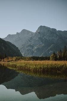 Lago refletindo a paisagem montanhosa, cercada por árvores e grama seca