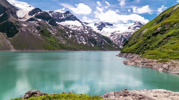 Lago stausee mooserboden cercado por montanhas sob a luz do sol em kaprun, áustria