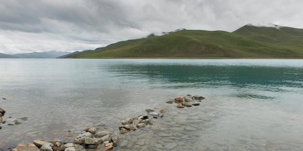 Lago yamdrok com montanhas ao fundo, nagarze, shannan, tibete, china