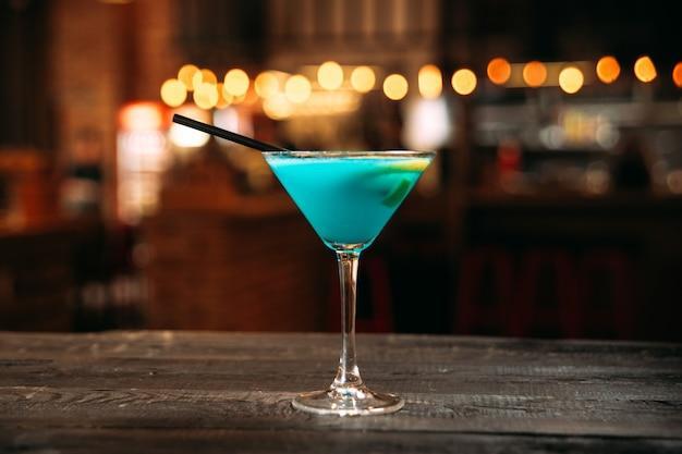 Lagoa azul doce cocktail com um canudo preto no copo de martini na mesa de madeira com fundo desfocado luzes de bokeh