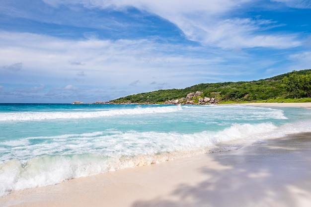 Lagoa azul e areia branca em um dia ensolarado de verão, na incrível praia tropical de anse source d'argent