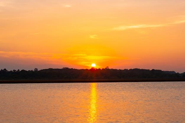 Lagoa de reflexão do sol. belo pôr do sol por trás das nuvens e céu azul acima da paisagem sobre a lagoa