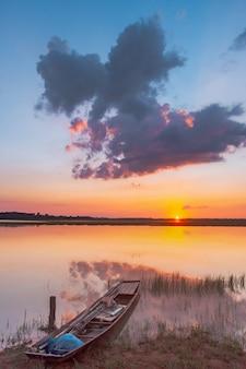 Lagoa de reflexão do sol. por do sol bonito atrás das nuvens e do céu azul acima da paisagem excedente da lagoa. céu dramático com nuvem ao pôr do sol