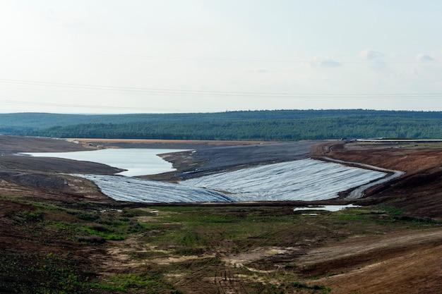 Lagoa de rejeito industrial em construção na paisagem com impermeabilização no fundo