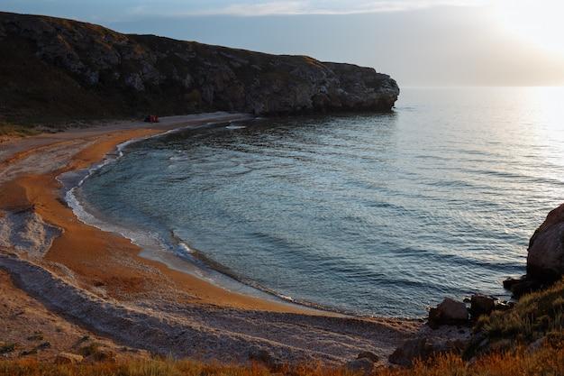 Lagoa do mar com uma praia de areia e uma tenda ao pôr do sol