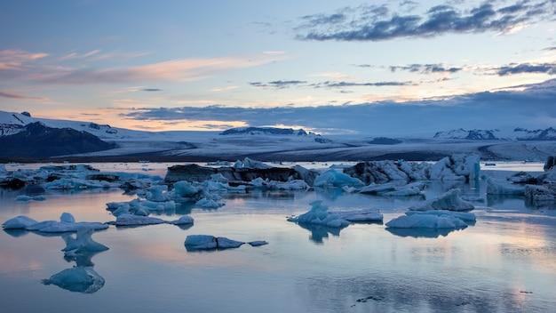 Lagoa glaciar ao amanhecer com gelo flutuando na água