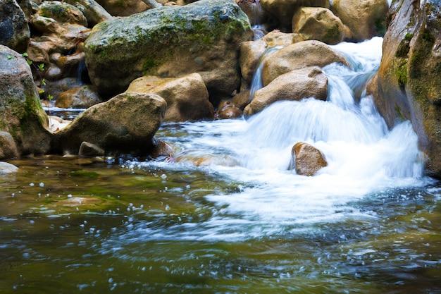 Lagoa verde clara de águas paradas cercada por pequenas cachoeiras e rochas em dia de verão