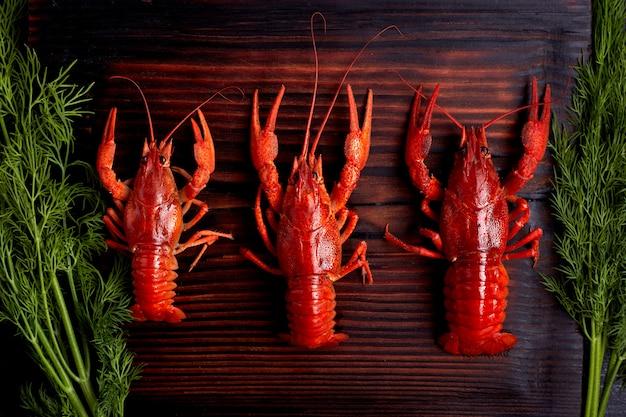 Lagosta cozida lagostins cozida pronta para comer no fundo escuro de madeira