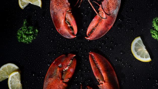 Lagosta vermelha com limão e salsa em fundo escuro.