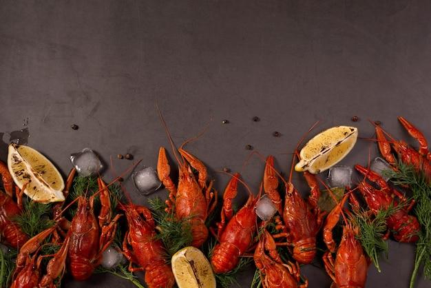Lagosta vermelha cozida pronta para comer com rodelas de limão e cubos de gelo em uma superfície preta