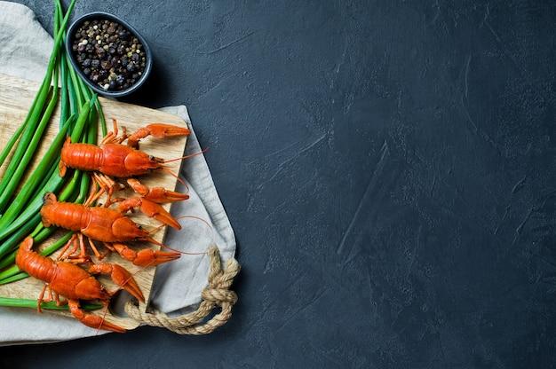 Lagostas cozidas em uma placa de desbastamento de madeira.
