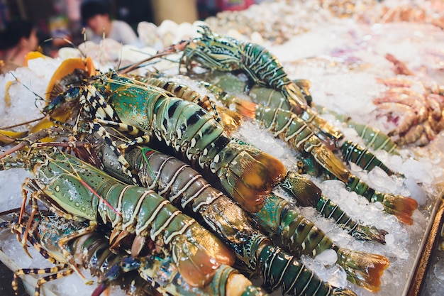 Lagostas frescas no gelo à venda no restaurante. foco seletivo na lagosta escura.