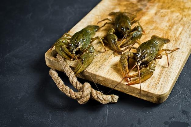 Lagostas vivas em uma placa de desbastamento de madeira.