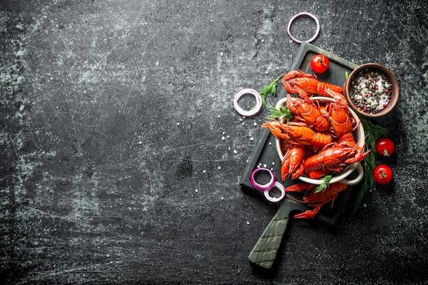 Lagostins cozidos em uma placa de corte com anéis de cebola, tomates e especiarias. em fundo escuro rústico