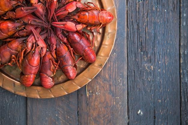 Lagostins cozidos vermelhos na mesa em estilo rústico