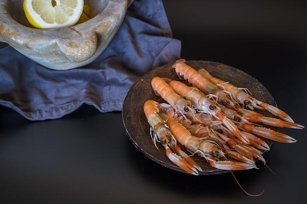 Lagostins crus deliciosos com um almofariz de pedra cheio de limões
