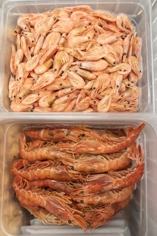 Lagostins e camarões crus congelados em um recipiente de plástico.