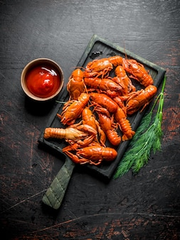 Lagostins vermelhos cozidos em uma tábua com molho e endro. em fundo escuro rústico