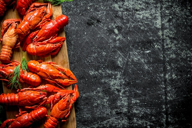 Lagostins vermelhos recém-cozinhados em uma placa de corte. em fundo escuro rústico