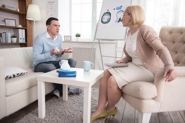 Lágrimas sinceras. homem ansioso e estressante se comunicando com psicólogo sênior enquanto chora